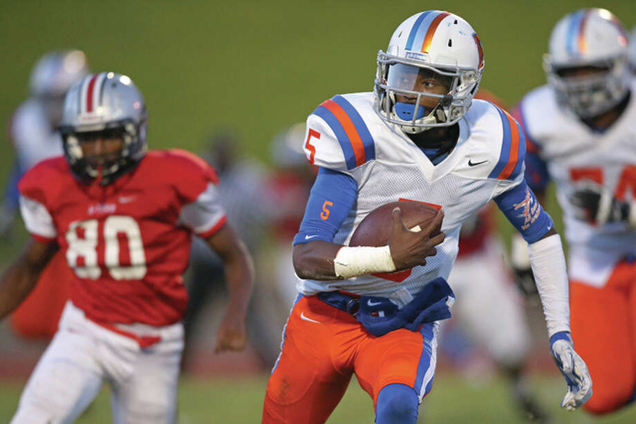 East St. Louis Flyers quarterback Reyondus Estes (5) runs for a big gain as Alton Redbirds defensive end Ronald Gilchrese (80) gives chase during the first half of Friday night's Southwestern conference football game at Public School Stadium in Alton. Photo: Billy Hurst | For The Telegraph