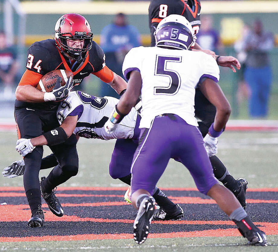 Jackson Morrissey of Edwardsville (34) picks up yardage against Collinsville's Max Lyons (5) in Friday night's Southwestern Conference game at the District 7 Sports Complex. Edwardsville won 33-7.