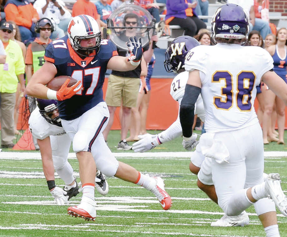 Tim Clary of Illinois (47) picks up yardage after catching a pass from Wes Lunt during action in Saturday's win over Western Illinois University at Memorial Stadium. At right is defender David Griffith of WIU. Photo: Cary Frye | For The Telegraph