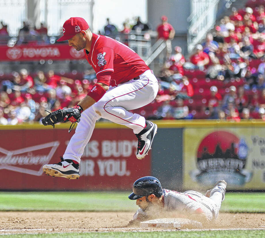 Reds first baseman Joey Votto leaps over the Cardinals' Matt Carpenter as Carpenter dives back to first base following a single during the fifth inning Sunday in Cincinnati. Photo: Associated Press