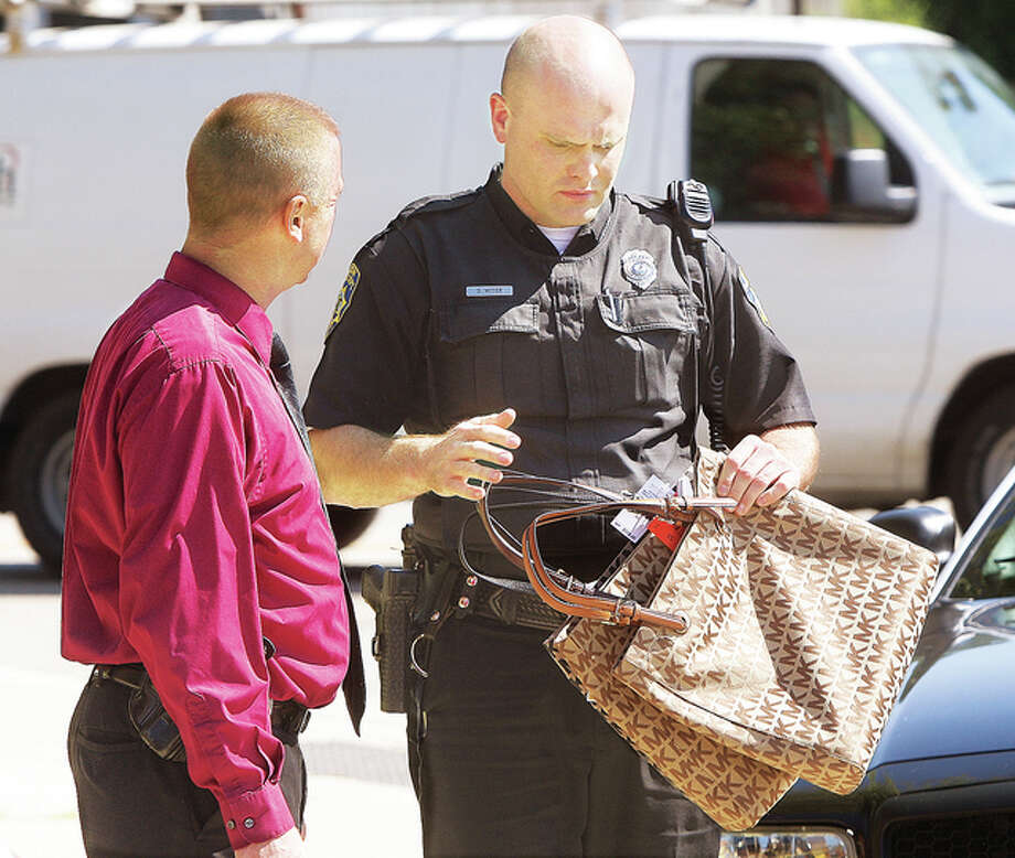 Alton Police Officer Derek Vetter, right, holds three of at least four identical handbags recoved from the car the woman was in as he talks to an Alton detective. The bags still had all of the store's tags still attached to them.