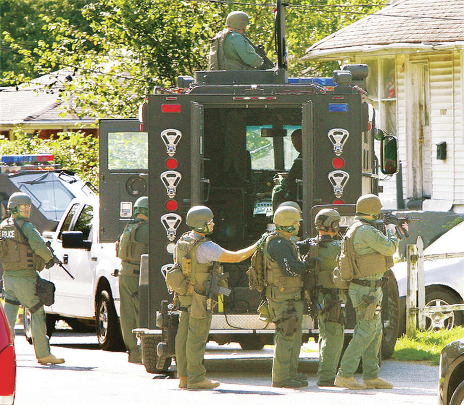 John Badman/The Telegraph Members of the ILEAS tactical team prepare to move to the rear of a house Thursday in the 1100 block of Putnam Street in Alton to execute a search warrant on a Jerseyville city case in which police were searching for one or more stolen guns. The neighborhood was blocked off as three armored vehicles, police cars and the ILEAS transport truck blocked the street. Several expolosions from flash-bang grenades could be heard going off as police entered the house.
