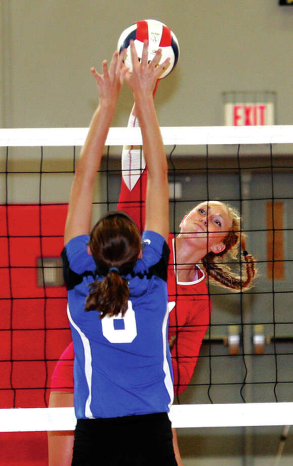 Alton's Annie Evans (back), shown getting a kill over the block of Columbia's Sydney Bullock in an Aug. 24 match at Alton High, had six kills in the Redbirds' three-set Southwestern Conference loss at East St. Louis on Thursday night. Photo: James B. Ritter / For The Telegraph