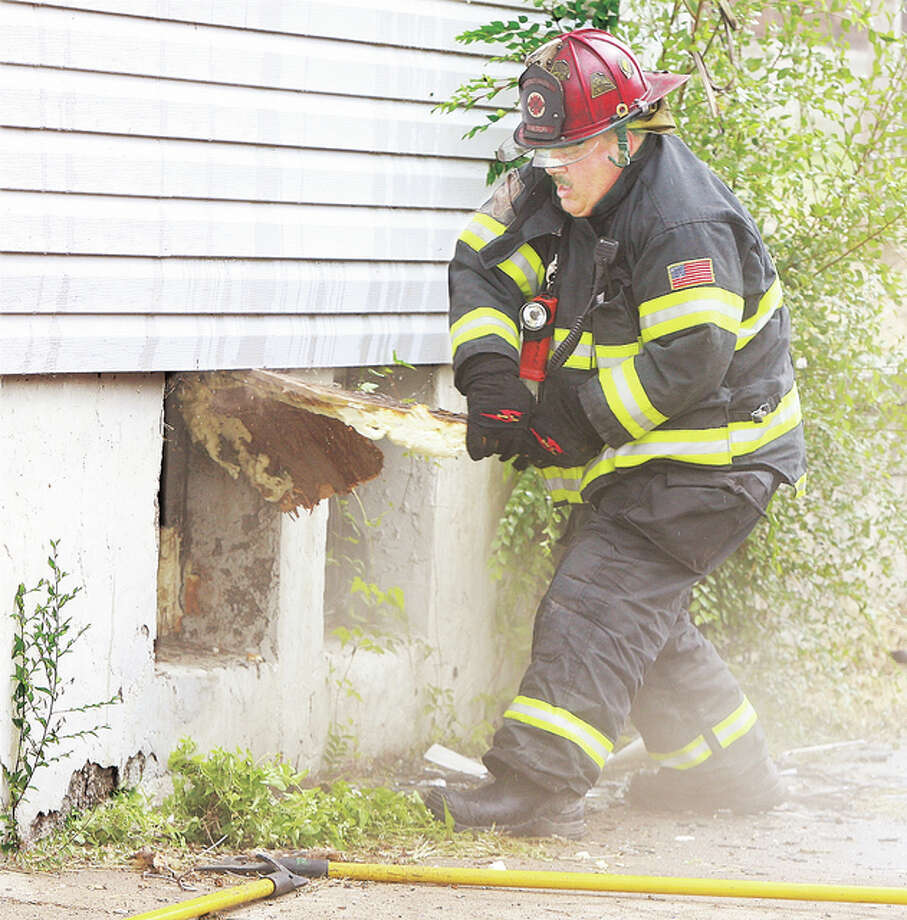 Alton Fire Department Captain Rick Orban battles a layer of insulation he was trying to remove from a basement window of the duplex in order to gain access to the basement from the front of the duplex. The duplex was unoccupied.