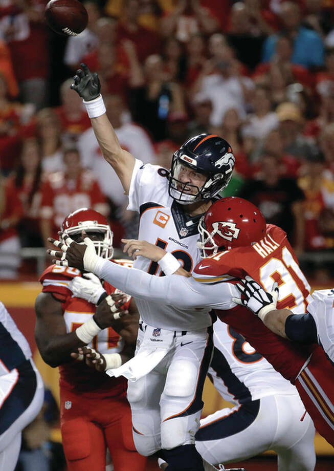 Denver Broncos quarterback Peyton Manning (18) throws under pressure from Kansas City Chiefs linebacker Tamba Hali (91) during the first half of an NFL football game in Kansas City, Mo., Thursday, Sept. 17, 2015. (AP Photo/Charlie Riedel)