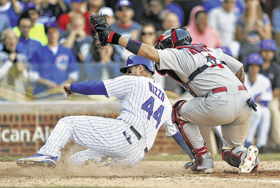 Cardinals catcher Yadier Molina (4) holds his glove up after tagging out the Cubs' Anthony Rizzo at home plate in the eighth Sunday at Wrigley Field. Photo: AP