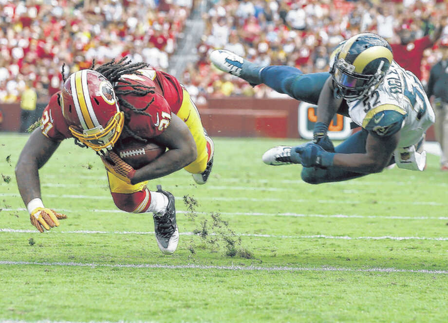 Washington Redskins running back Matt Jones (31) dives for extra yardage after breaking a tackle by Rams outside linebacker Alec Ogletree Sunday in Landover, Md.