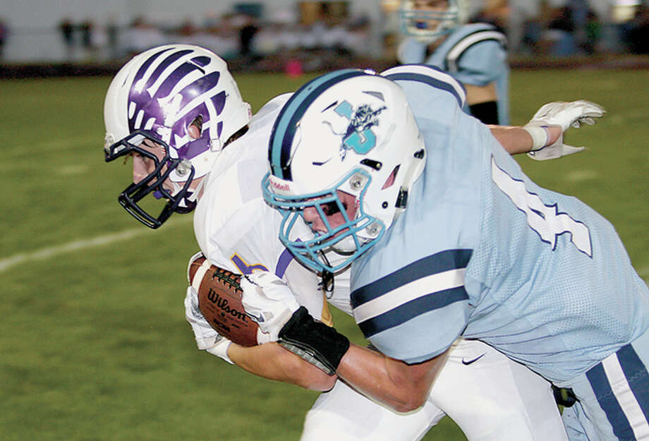 After making a first down, CM's David Lane is pulled down by Jersey's Logan Metzler Friday. Photo: James B. Ritter | For The Telegraph