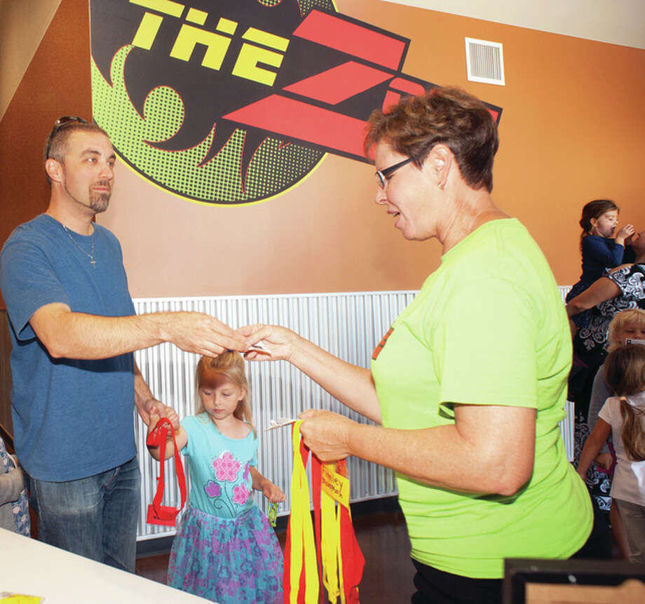"""Anne Davis, right, checks children into """"The Zone"""" at Faith Fellowship Church. The Zone allows children to learn about God, while adults attend the Sunday morning service."""
