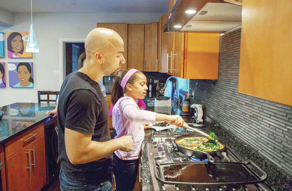 Taryn Robinson cooks white turkey chili, a meal kit dish from Blue Apron, as her father, Keith Robinson, watches over her shoulder in Evanston, Ill. Meal kits are fairly new in the U.S., first appearing in the country about four years after first gaining popularity in Europe. The industry is growing quickly and competition is heating up as more players enter the space and fight to gain customers.
