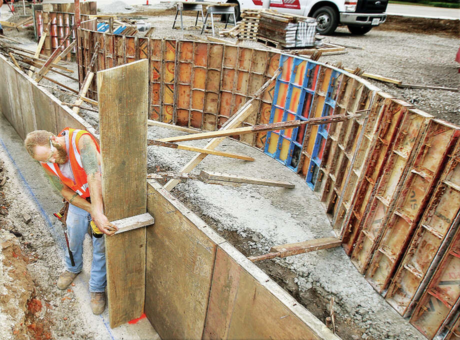 A worker from RCS Construction in Wood River sets up curved forms on the east side of the Ardent Mills near the entrance to the Argosy Casino in Alton as work continues on the construction of a flood memorial on the city owned parking lot.