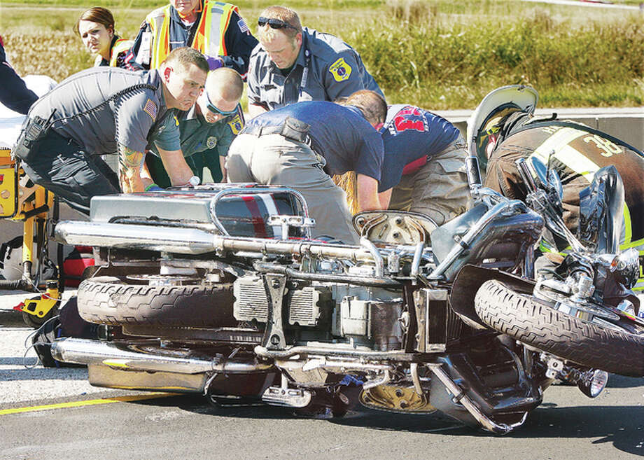 Rescue workers, including Hartford firefighters, Alton Memorial Ambulance paramedics and ARCH Air Medical Services Inc. flight nurses, lift the driver of a Harley-Davidson motorcycle onto an ARCH stretcher in the middle of the northbound lanes of Illinois Route 3 about one eighth of a mile south of Piasa Lane in Hartford Wednesday. The subject was seriously injured when his bike crashed into the rear end of a pickup truck.