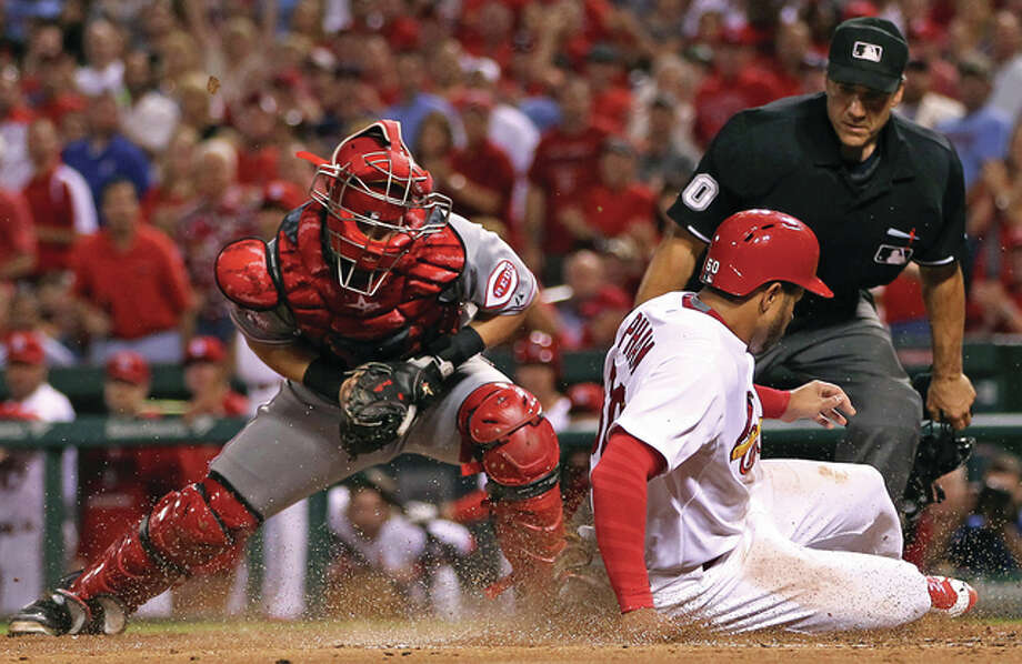 The Cardinals' Tommy Pham (right) slides in safely ahead of the tag from Reds catcher Tucker Barnhart as he scores on a double by Matt Holliday during the third inning Wednesday night at Busch Stadium. Photo: Billy Hurst / For The Telegraph