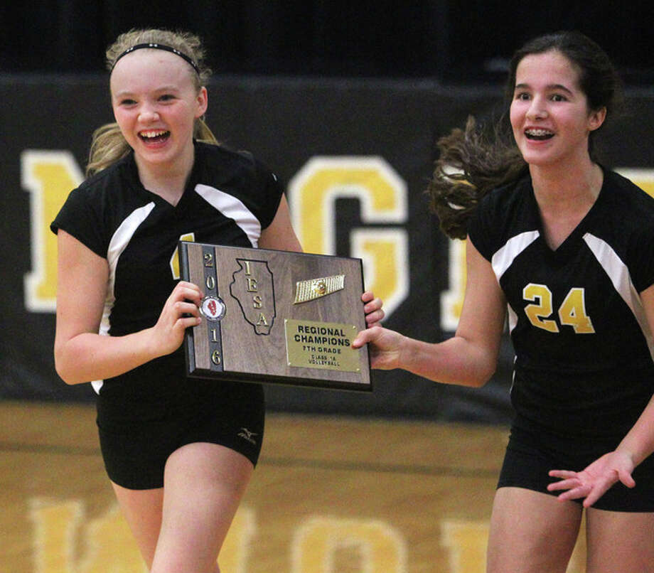 A-C Central volleyball players Addyson McClure (left) and Bailey Wallbaum run back to their teammates after accepting the A-C Central Regional championship plaque. The Lady Knights seventh-graders beat Virginia for the regional title. Photo: Dennis Mathes | Journal-Courier