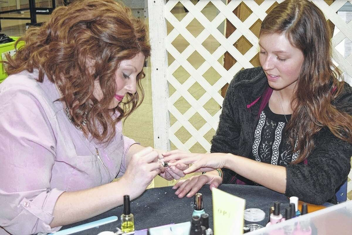 """Jeslynn Walker (right) of Geneva, a junior at MacMurray College, receives a manicure Thursday from Casey Jackson of Jacksonville. It was a part of MacMurray College's """"de-stressing"""" program for students."""