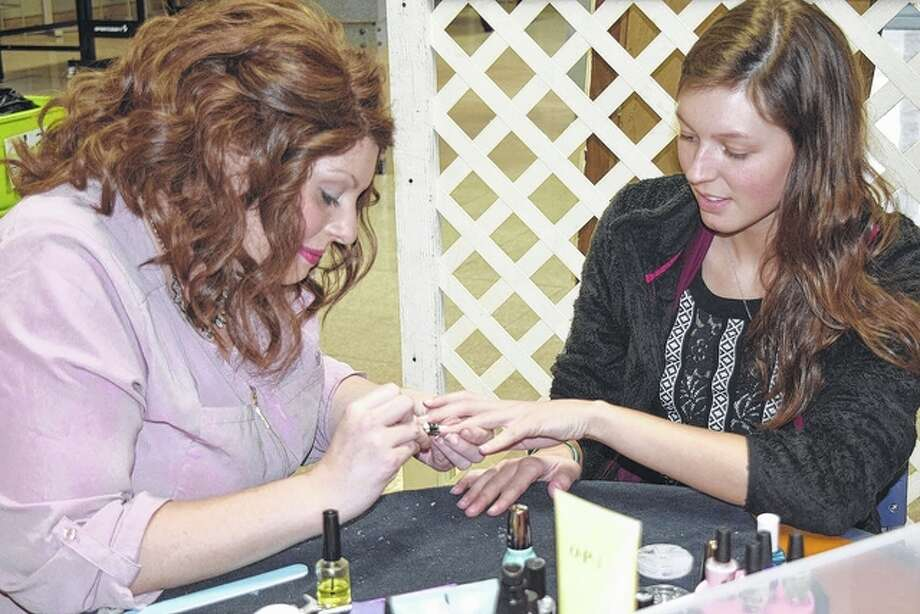 """Jeslynn Walker (right) of Geneva, a junior at MacMurray College, receives a manicure Thursday from Casey Jackson of Jacksonville. It was a part of MacMurray College's """"de-stressing"""" program for students. Photo: Samantha McDaniel-Ogletree 
