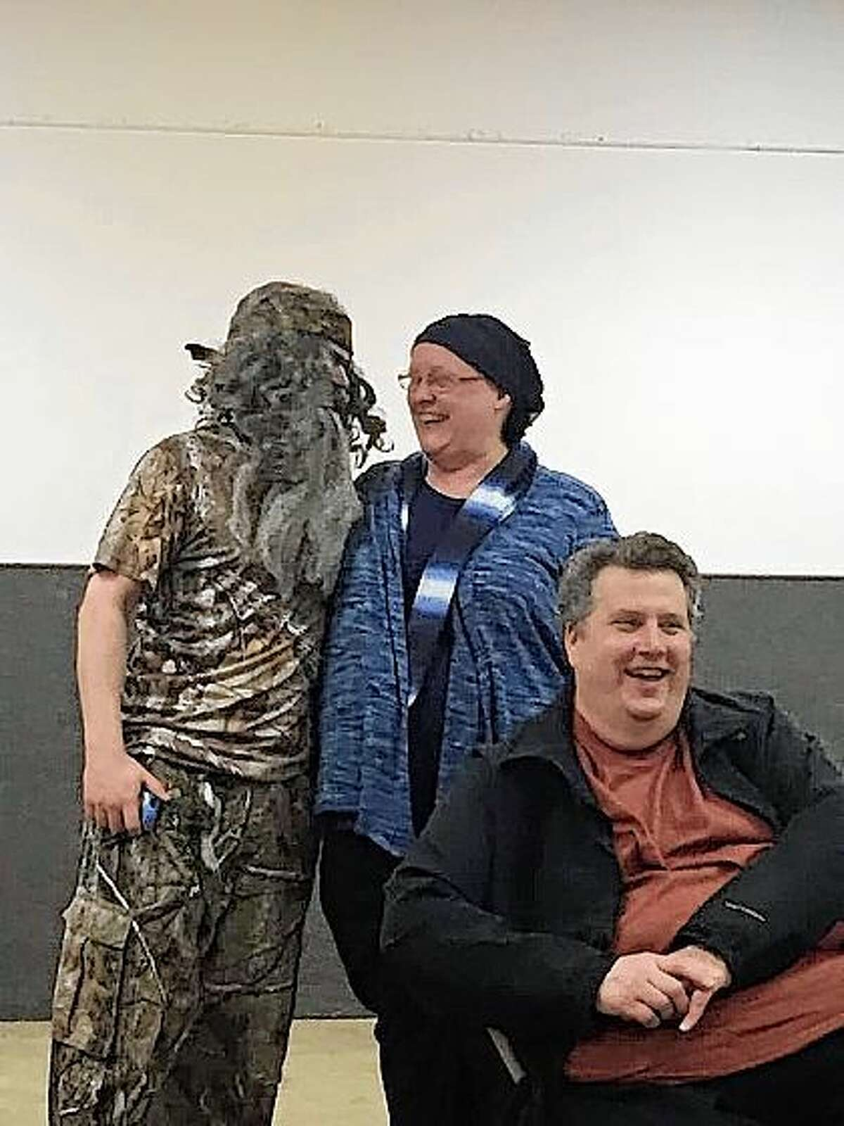 Momma Kay (portrayed by Donna DeWitt) shares a comical embrace with Phil Robertson as Frank DeWitt (front) conveys his amusement at her willingness to kill for $100,000 to re-style their basement!
