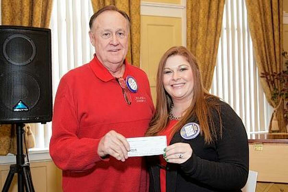 Chet Wynn, acting on behalf of the Jacksonville Rotary Club and Jacksonville Rotary Club Foundation, presents Brittany Henry with a $500 donation to the Governor Duncan Mansion.