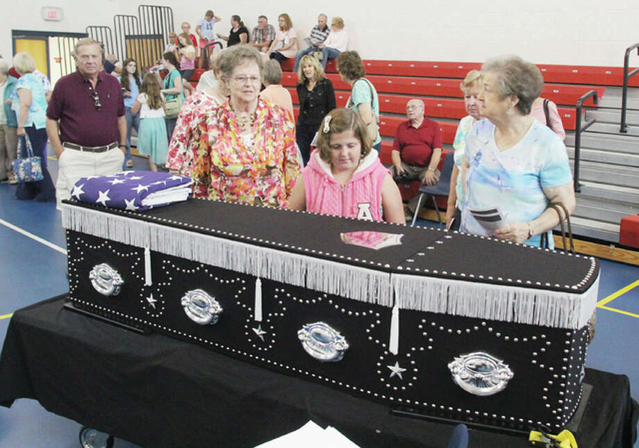 "People, including Grafton Alderman Bobbie Amburg, far right, look at a reproduction of Abraham Lincoln's coffin at the event ""Honoring Lincoln,"" a program at Grafton Elementary School, Sunday afternoon. The program, by the Grafton Historical Society, was about the coffin and Lincoln's final journey from Washington, D.C. to Springfield after his assassination."