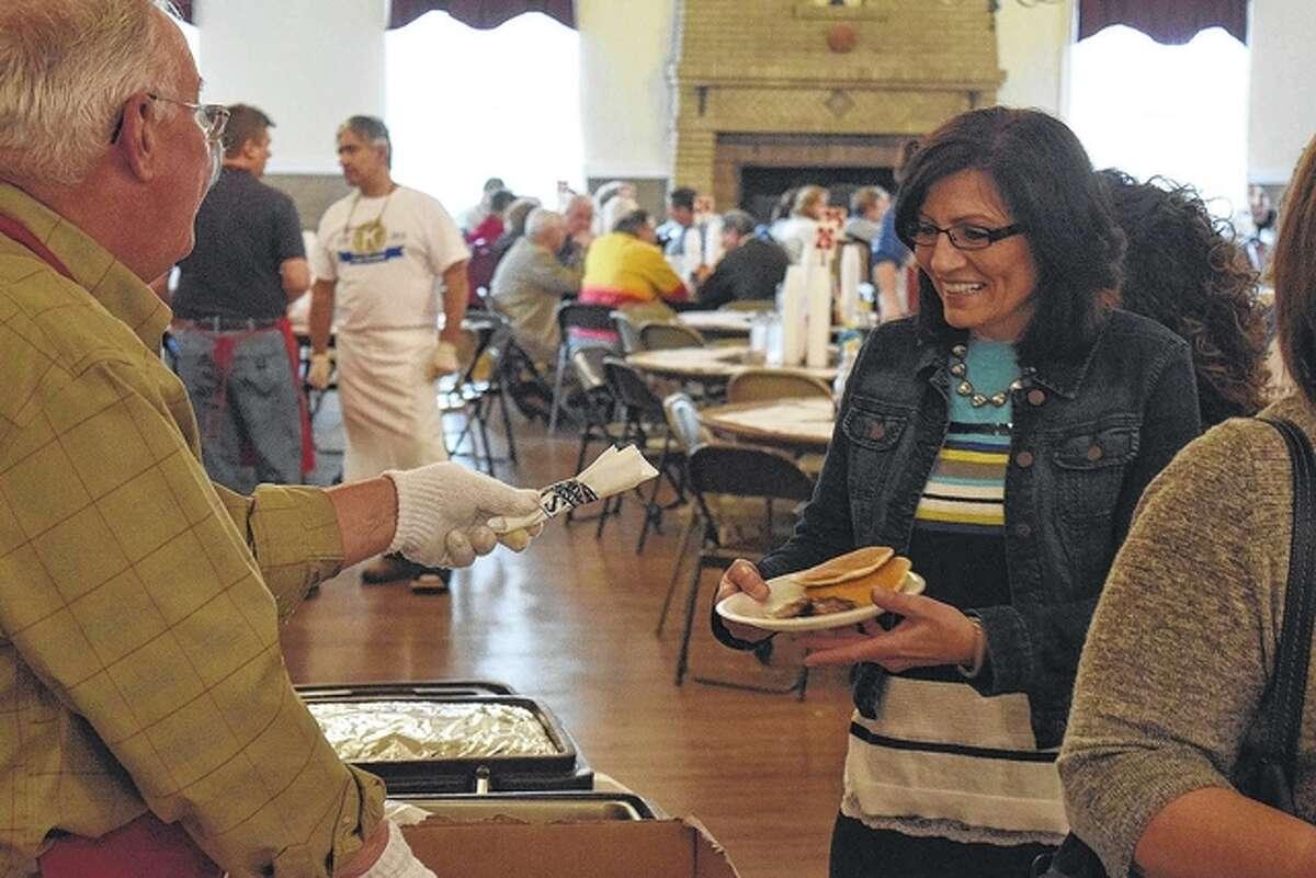 A patron at Kiwanis Pancake and Sausage Day receives eating utensils from Kiwanis member Bill Meier.