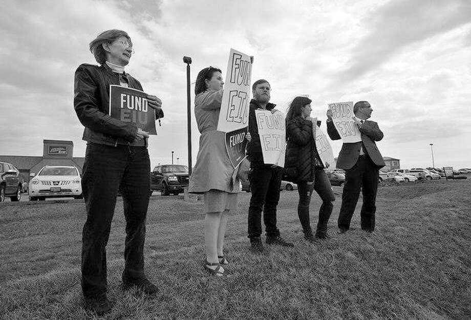Fund EIU supporters hold signs as they stand near the Stadium Grill in Mattoon. The protesters greeted Gov. Bruce Rauner when he arrived Monday for a campaign stop for U.S. Rep. John Shimkus. Eastern Illinois University in nearby Charleston is struggling with the state budget impasse that has impeded allocating state funding for higher education. Photo: Kevin Kilhoffer | Journal Gazette/Times-Courier (AP)
