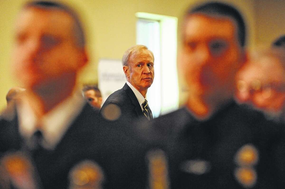 Governor Bruce Rauner waits Tuesday to pay his respects behind a line of law enforcement officers attending the visitation for Officer Fitzgerald at the First Christian Church in South Jacksonville.