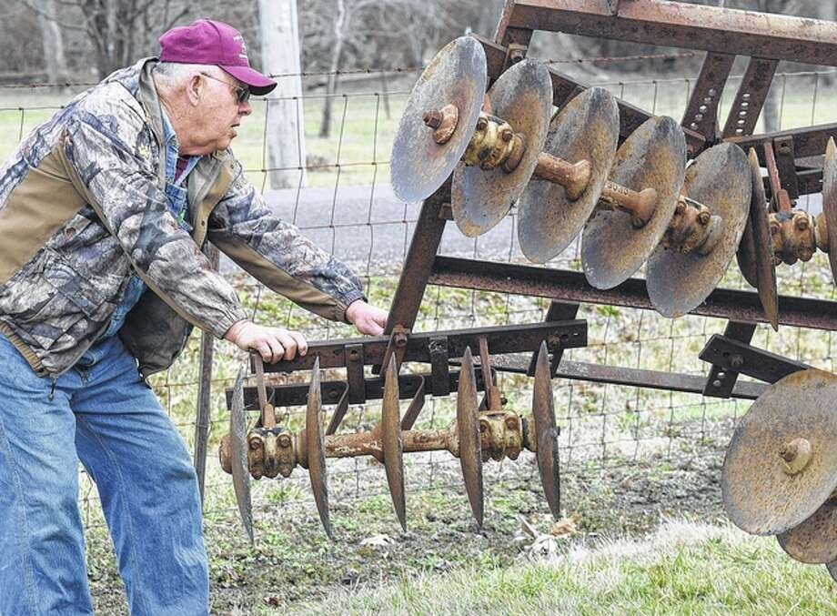 Prairie Land Heritage Museum Institute volunteer Dale Lair helps guide a piece of farming equipment into place for display at the museum grounds. Hundreds of items are being sold Saturday at a consignment sale that will benefit the preservation group. Photo: David C.L. Bauer | Journal-Courier