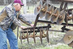 Prairie Land Heritage Museum Institute volunteer Dale Lair helps guide a piece of farming equipment into place for display at the museum grounds. Hundreds of items are being sold Saturday at a consignment sale that will benefit the preservation group.