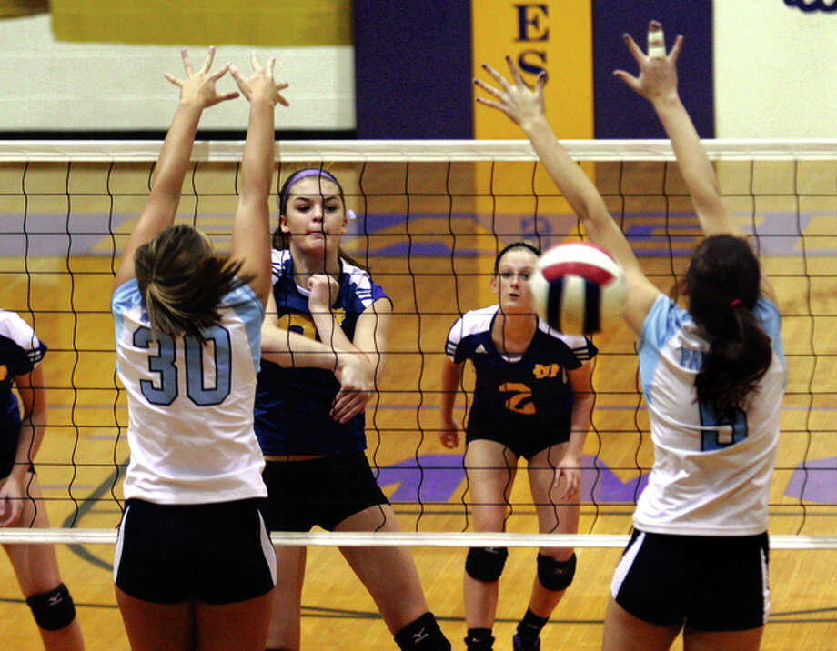 CM's Hannah Schmidt (middle, left) records a kill as she splits the block of Jersey's Aly Varble (left) and Olivia Nairn (right) while CM's Annika Ochs (middle, right) covers the play from the back row in Tuesday night's Mississippi Valley Conference volleyball match in Bethalto. Photo: James B. Ritter / For The Telegraph