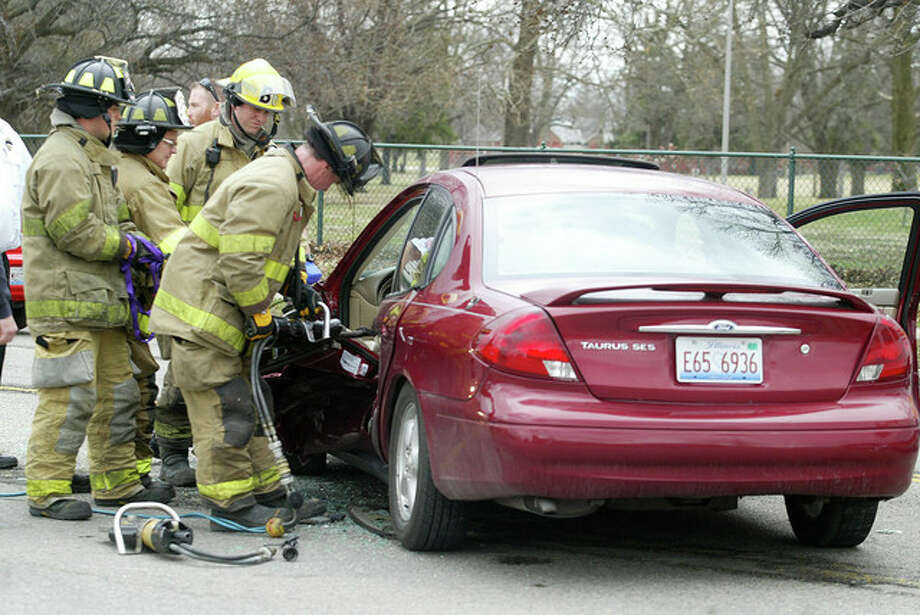 Jacksonville firefighters remove the door from one of two vehicles involved in an accident about 12:49 p.m. Wednesday in the 500 block of West Morton Avenue. Two people were hurt. Kendra B. Graham, 23, of Jacksonville was treated at Passavant Area Hospital and released after her vehicle and one being driven by Chelsea D. Adams, 21, of Jacksonville collided. A 3-year-old passenger was treated at the scene. Graham was cited on a charge of failure to yield, according to police. Photo: Samantha McDaniel-Ogletree | Journal-Courier