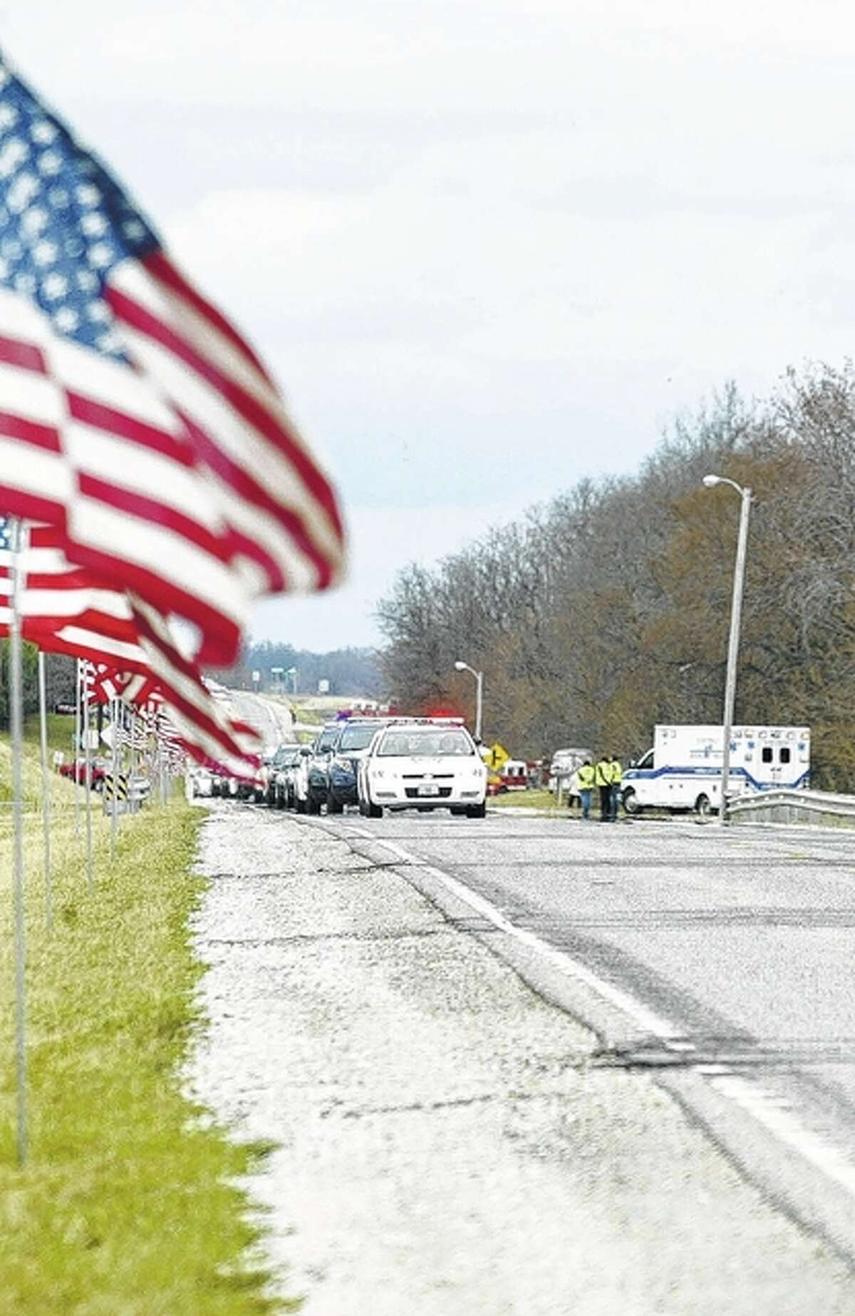 Law enforcement vehicles from across the state process along South Main Street following the funeral of South Jacksonville Police Officer Scot Fitzgerald. The line of vehicles stretched for several miles as emergency officials made their way to Murrayville for the officer's burial.