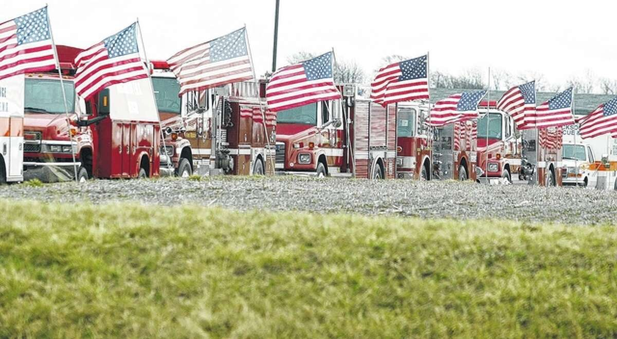 Firetrucks adorned with flags line up outside First Christian Church.