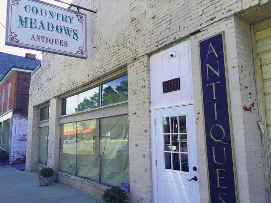 Country Meadow Antiques at 401 Broadway Ave. in Alton rests in a morning shade Tuesday morning. The display window will be revealed at 11 a.m. Saturday when they reopen after several months of renovation following a fire.