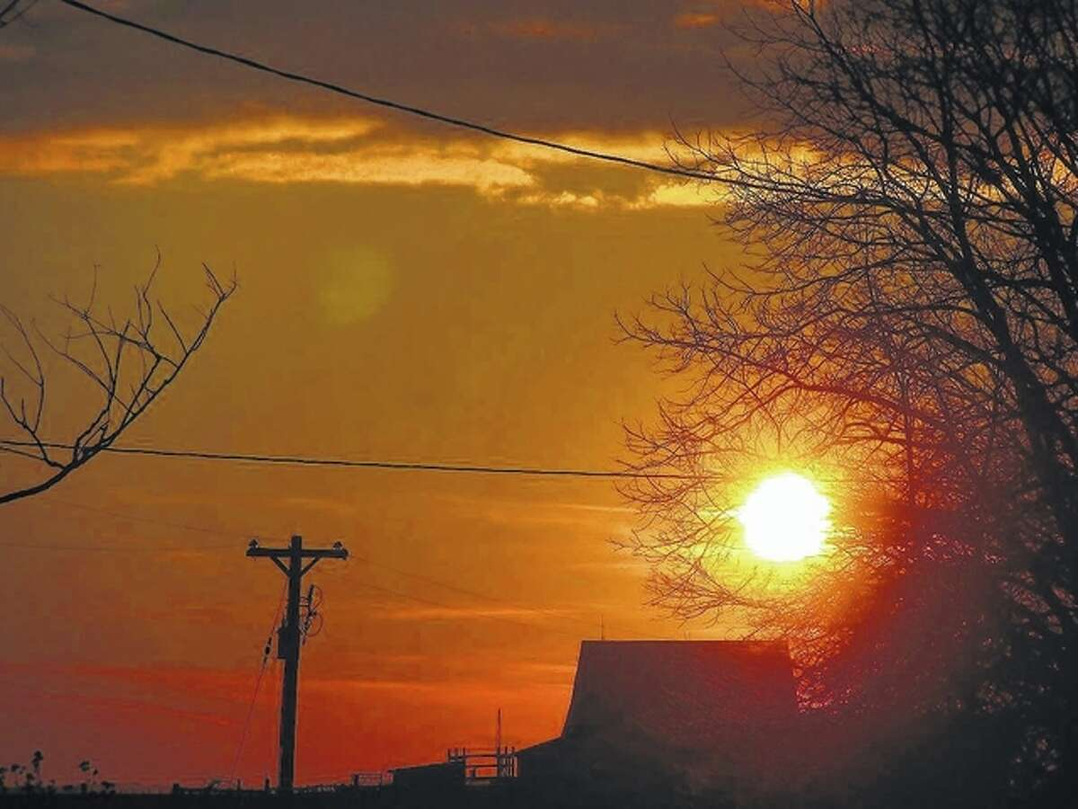 The sun sets over a barn in Scottville. The days will start seeming longer today, after much of the nation moved their clocks forward an hour overnight.