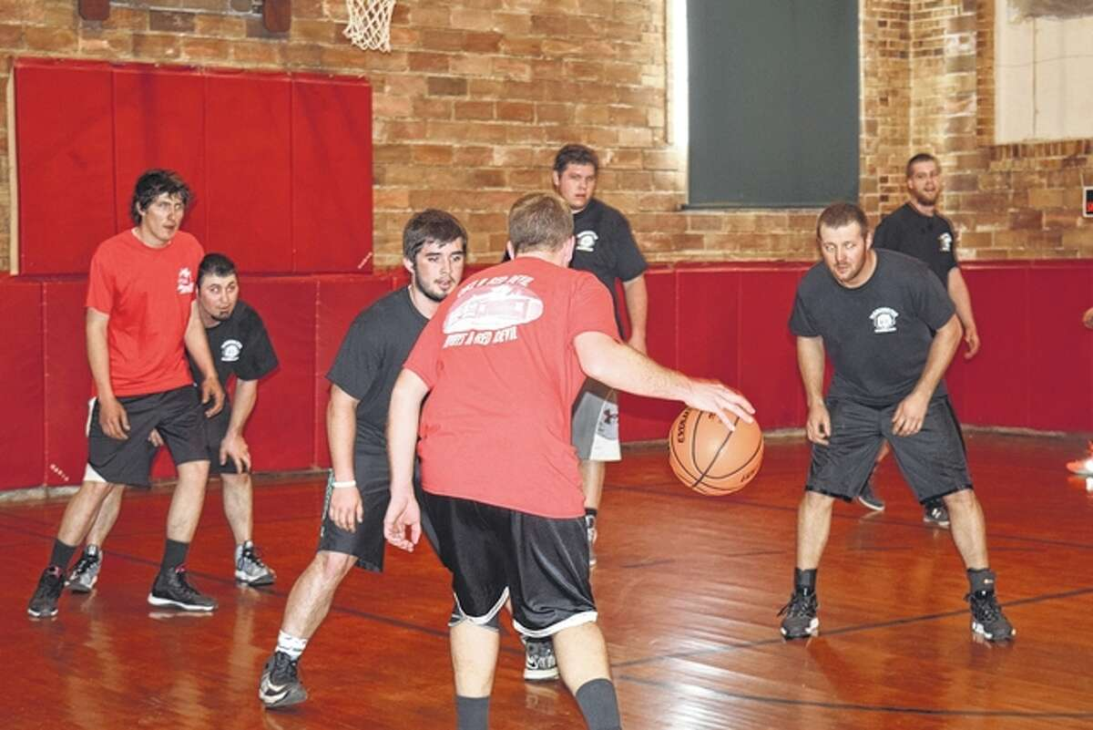 Players from the Manchester Blackhawks and Alsey Red Devils play Saturday during the 20 to 29-year-old category of the Old Timers Basketball competition to raise money for repairs for the Alsey Grade School gym.
