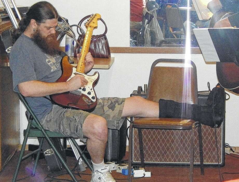 Not one to let a broken ankle stop him, guitarist Brett Moffitt plays Sunday at American Legion Post 279 in Jacksonville. Moffitt joined guitarists Larry Ford and Gary Becker and vocalist Aubrey Reed during the post's Sunday Funday, which features music and other activities on Sunday afternoons. Photo: Angela Bauer | Journal-Courier