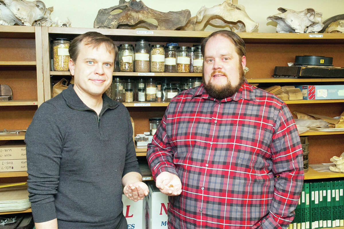 University of South Dakota-Vermillion assistant professor Matthew Sayre (left) and student Aaron Mayer, who are researching the Wari people of Peru, hold seeds from that part of the world that inspired a new craft beer called Wari.