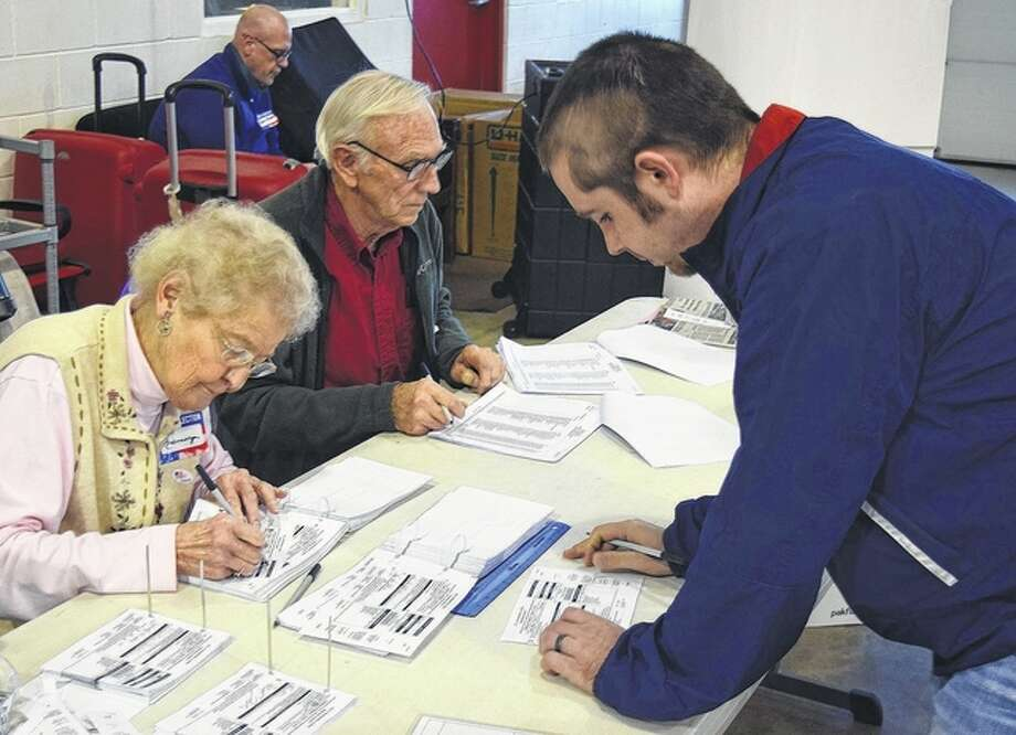 Election judges Rosemary Miller (from left) and Merle Megginson help Nick Flynn pick up a primary election ballot Tuesday at South Jacksonville Precinct 1 in the South Jacksonville fire station. The fire station serves as the polling place for South Jacksonville precincts 1, 2 and 3 and Pisgah precinct, all of which saw a steady stream of voters. Photo: Greg Olson | Journal-Courier