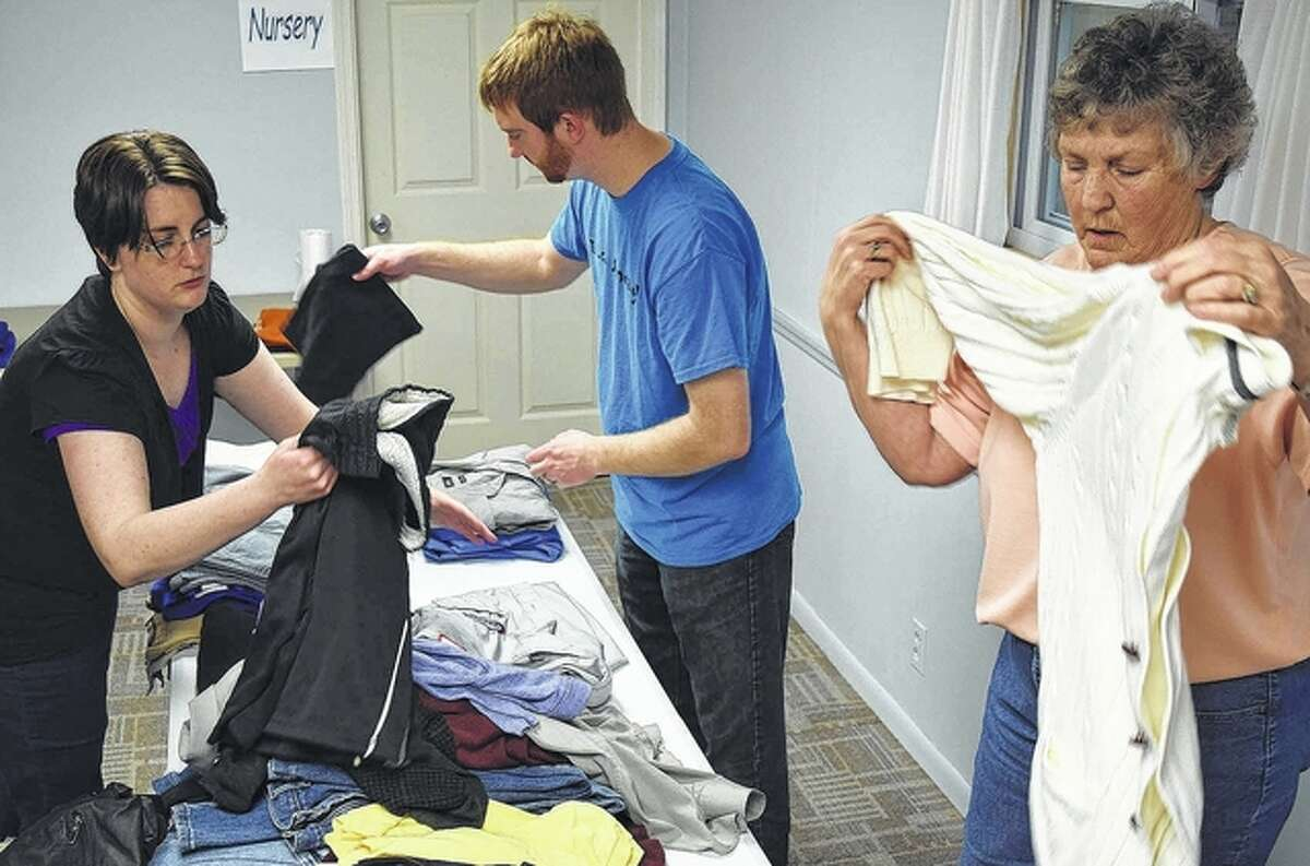 Share the Love volunteers Amy Barbee (from left), Community Christian Church Pastor Tim Barbee and Lucy Myers sort clothes that will be distributed to the needy April 2 at the Share the Love event at Spirit of Faith Soup Kitchen and Community Center in Jacksonville.