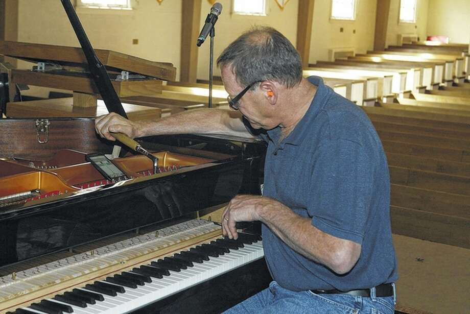 Tom Kaplan, a piano service technician, tunes a grand piano Thursday in Rammelkamp Chapel in preparation for a performance Saturday. Photo: Samantha McDaniel-Ogletree | Journal-Courier