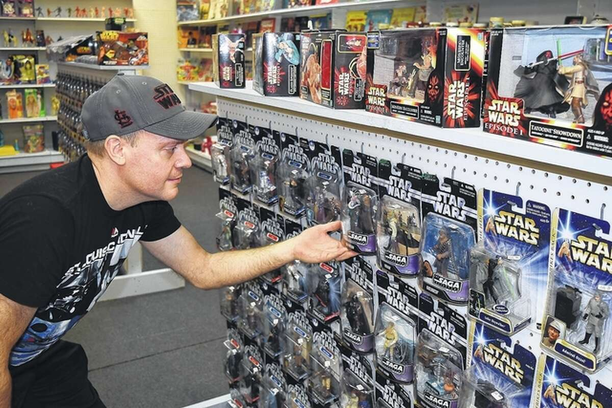 """Mark Medley of Jacksonville looks at some of the many """"Star Wars"""" items he has for sale in his new collectibles shop - Destination Toys - at 314 S. Main St., which will open for business this weekend."""
