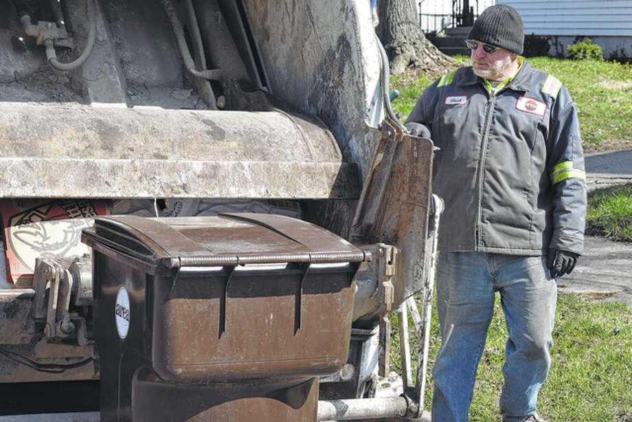 Area Disposal employee Chuck Jennings loads his truck with garbage early Monday.