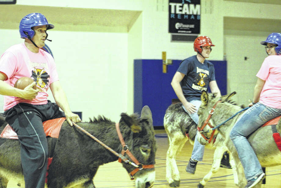 MacMurray College students and faculty played a staff vs. students donkey basketball game Thursday evening. The players attempted to ride donkeys while playing the game. Photo: Samantha McDaniel-Ogletree | Journal-Courier