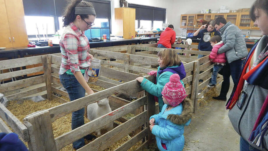 Virginia FFA members Hannah Krause (from left), Dylan McGlasson and Ben Krause talk with Virginia pre-kindergarten students about petting zoo animals during FFA Week. Photo: Nick Draper | Journal-Courier