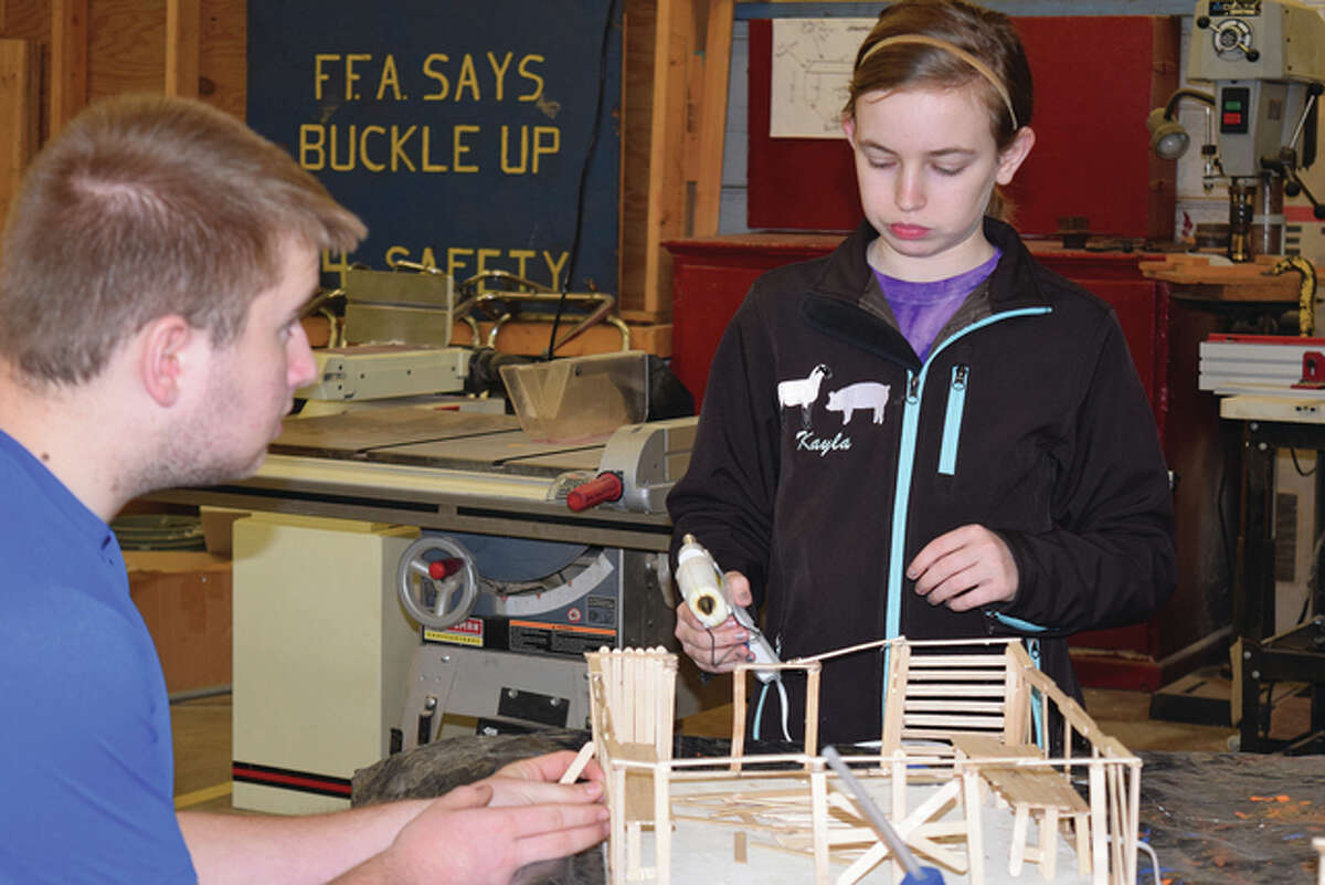 Kayla Keeton (right), a freshman at Franklin High School, and junior Colby Myer work on model greenhouses during their agriculture class.
