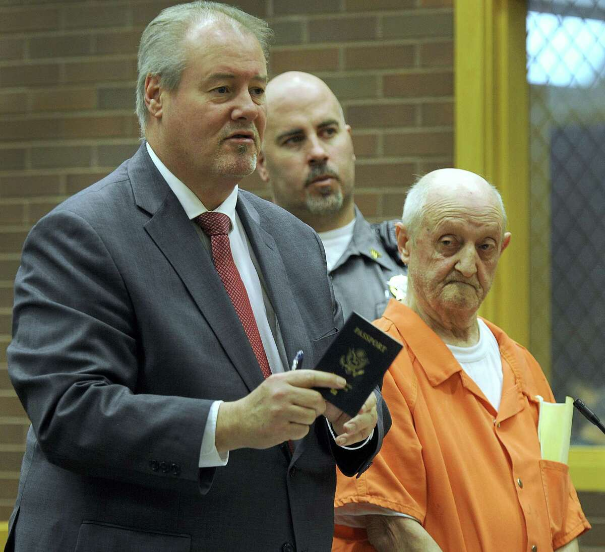 Attorney Edward Gavin shows William Tefzger's passport at a bond hearing at state Superior Court in Danbury on Tuesday.