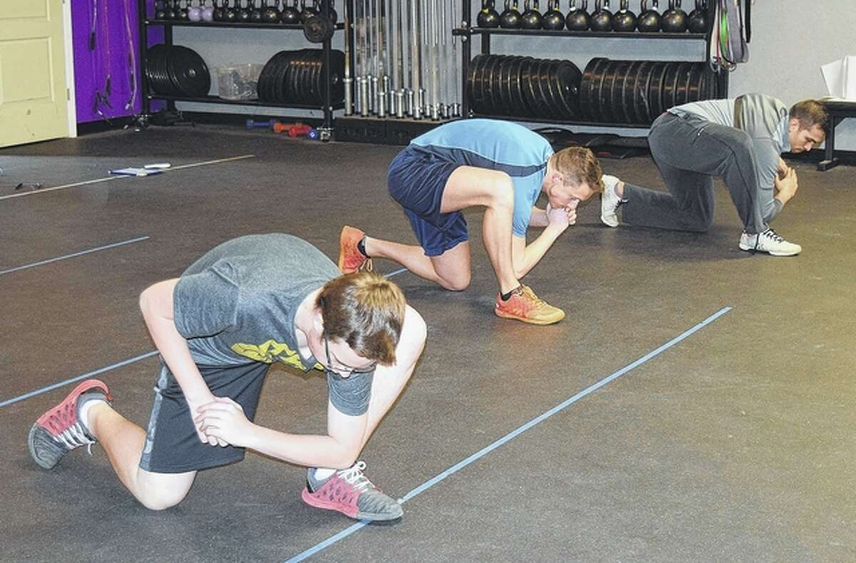 Turner Reed (from left), Jacob Mattes and Ricki Radilla do lunges during a CrossFit class Friday at the Bob Freesen YMCA.
