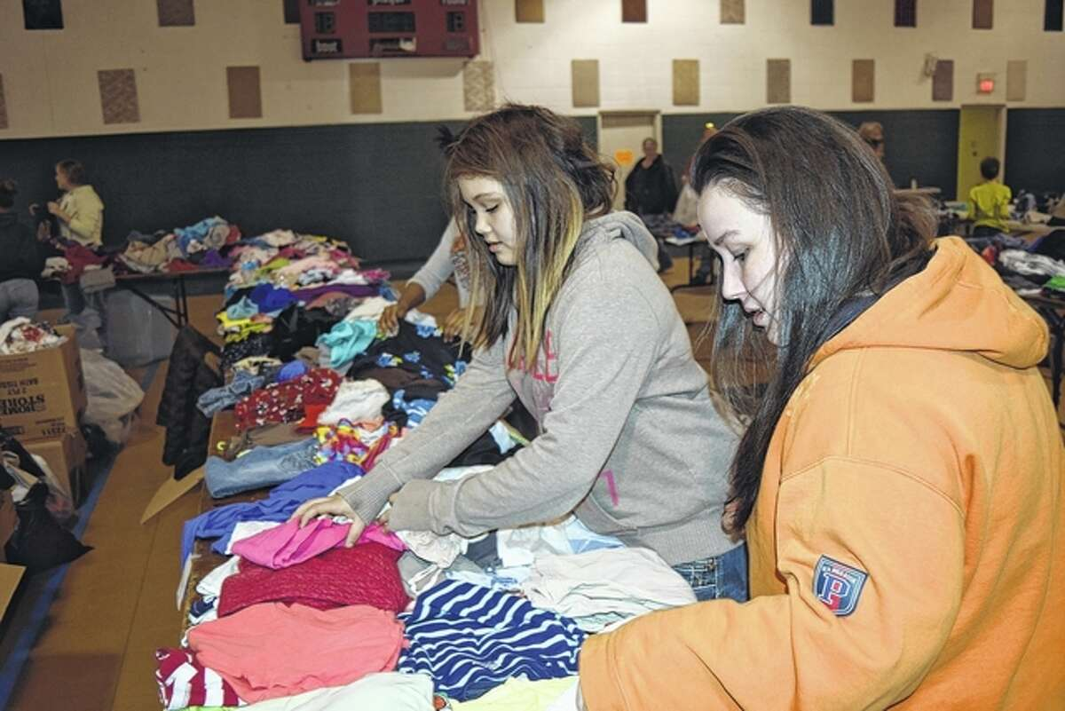 Jazmyn Nunez of Jacksonville (left) and Tiffany Tracy of Jacksonville look through some clothes Saturday at the Share the Love event at Spirit of Faith Soup Kitchen and Community Center.
