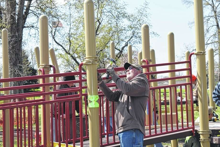 Elks Club member Rick Peck helps install new playground equipment in Community Park on Tuesday. It is handicap-accessible. Photo: Samantha McDaniel-Ogletree | Journal-Courier