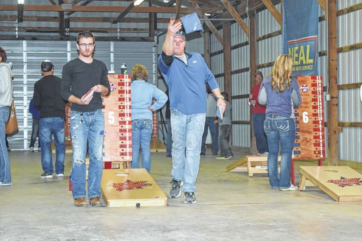 Christopher Drew of Springfield (left) and Jeremy Wells of Winchester toss bags Saturday in the fifth annual Toss for Autism bags tournament at the Morgan County Fairgrounds. Proceeds from the event go to help the educational needs of autistic students in School District 117.